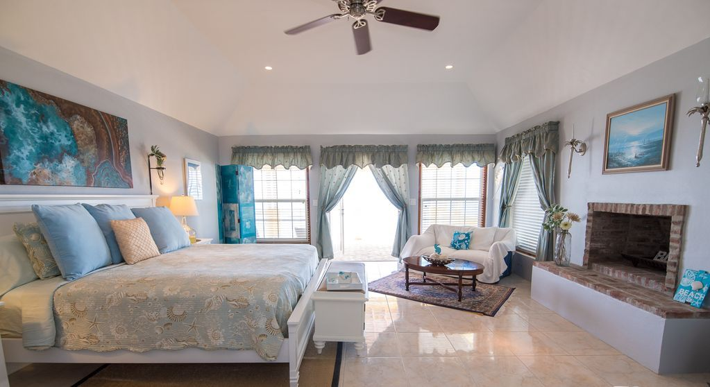 Large master bedroom  opens on deck overlooking beach and includes a fireplace.