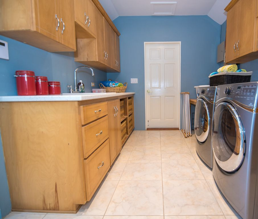 Full-service laundry room with sink and new stainless steel appliances.